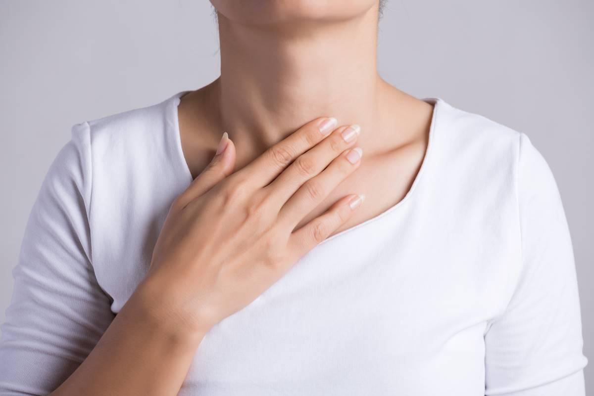 mujer tocando garganta